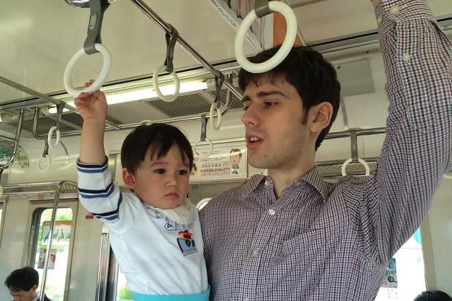 Баща и син в градския транспорт в Токио.