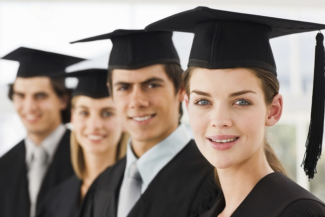 Closeup of happy young graduate men and women in a row