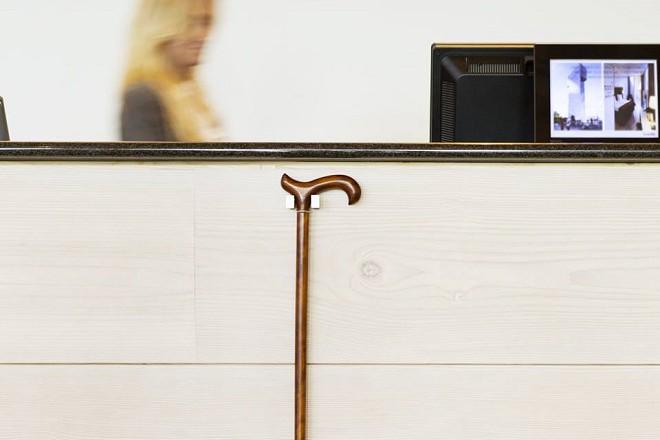 Ето как един възрастен човек може да окачи бастуна си, докато чака на рецепцията в достъпна верига хотели.