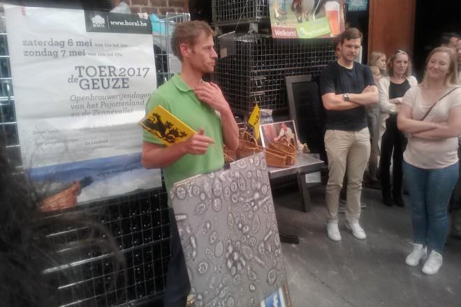 собственикът на DeCam (до реката Дендер) и постер с микроорганизмите