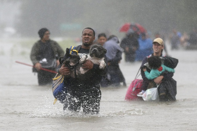 Isiah Courtney carries his dog Bruce through flood waters from Tropical Storm Harvey in Beaumont Place